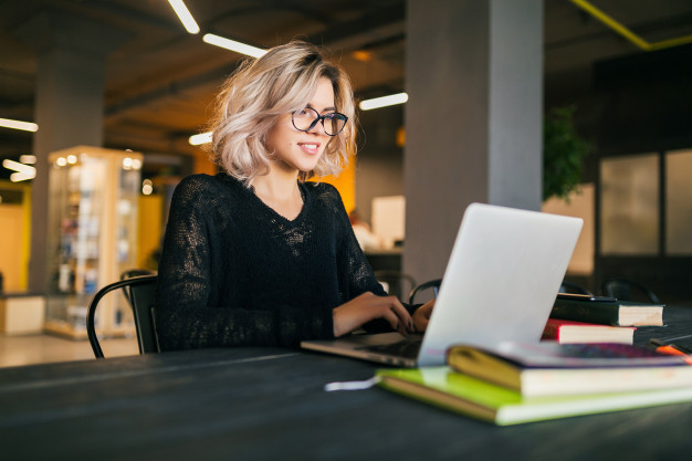 portrait-young-pretty-smiling-woman-sitting-table-black-shirt-working-laptop-co-working-office-wearing-glasses_285396-79